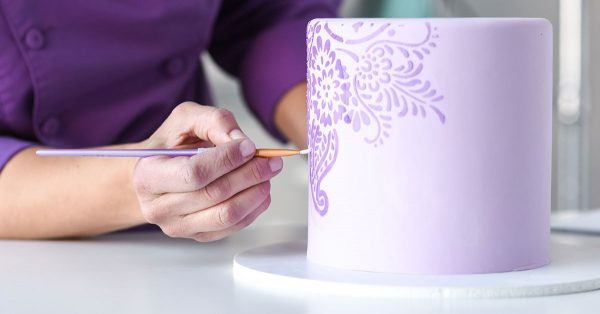 Painting a flower design on a purple cake