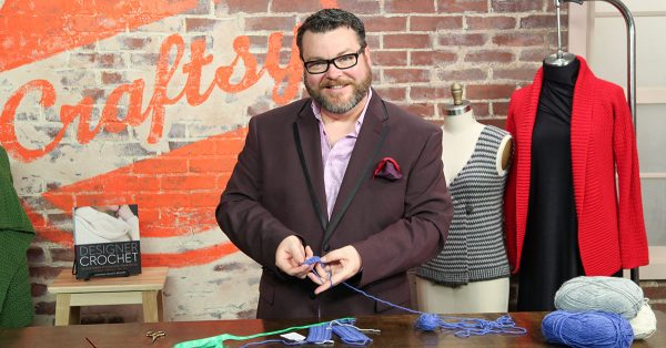 Man in glasses smiling and knitting with blue yarn