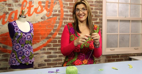 Woman standing and knitting with green yarn
