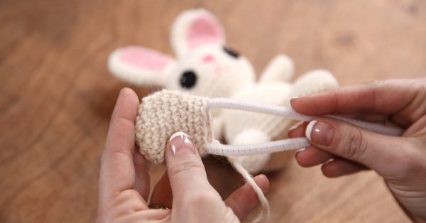 Putting a pipe cleaner in a small knit paw