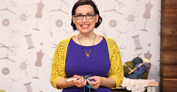 Woman with a purple shirt smiling at the camera and knitting