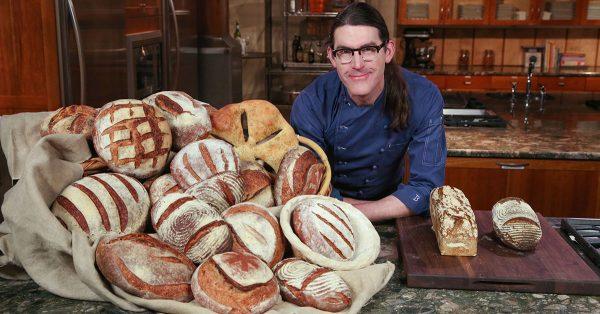 Man posing near pile of bread