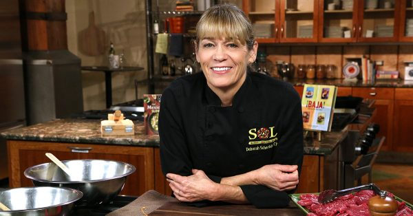 Woman in a chef's coat near a stove looking at camera