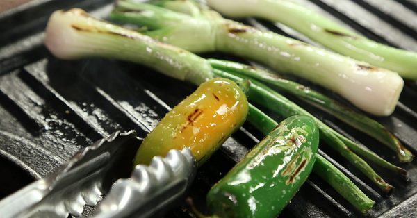 Peppers and chives being grilled