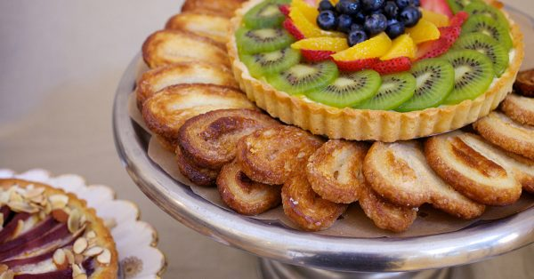 Fruit tart surrounded by pastries