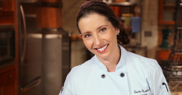 Woman in a pastry chef jacket smiling at camera