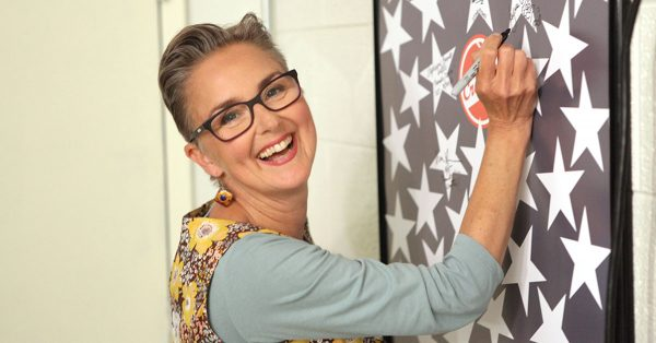 Woman signing a poster and smiling