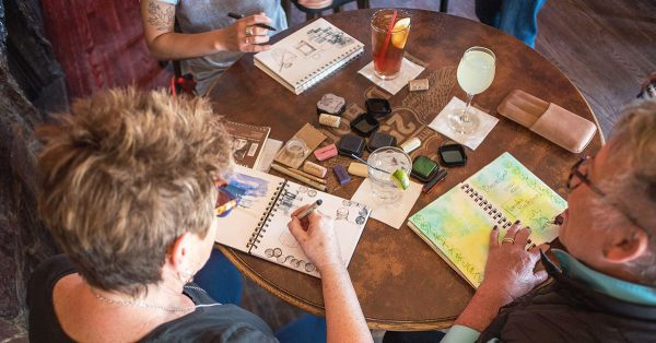 People sitting at a table sketching