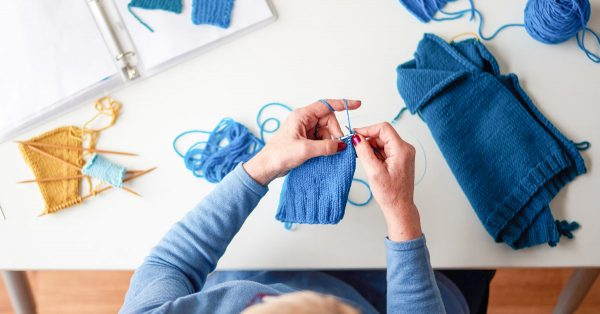 Person knitting with blue crochet