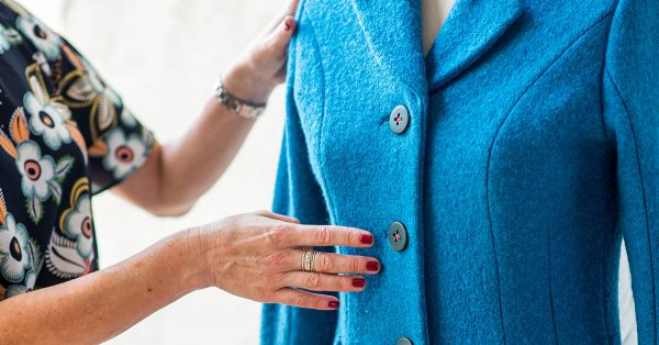 Woman's hands in front of a blue jacket