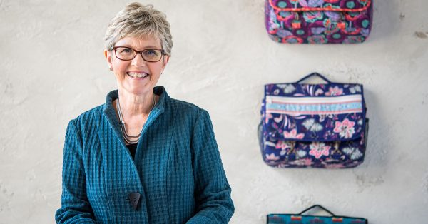 Woman posing in front of patterned messenger bags