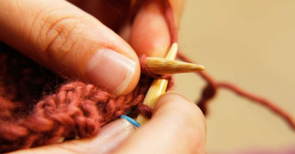 Close up of person sewing with rust colored yarn