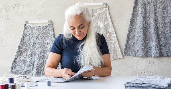 Woman with long white hair sewing