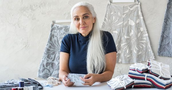 Woman with white hair holding fabric squares