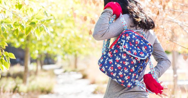 Woman putting on a blue flower backpack