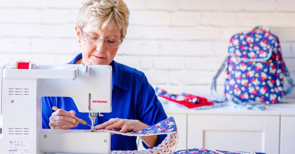 Woman sewing colorful fabric on sewing machine
