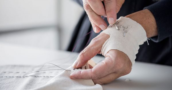 Person adding beading to their sewing
