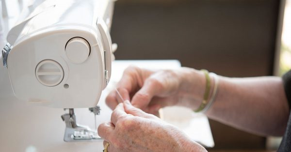 Person holding thread new sewing machine