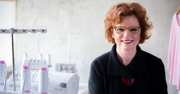 Woman with short red hair and glasses smiling at the camera