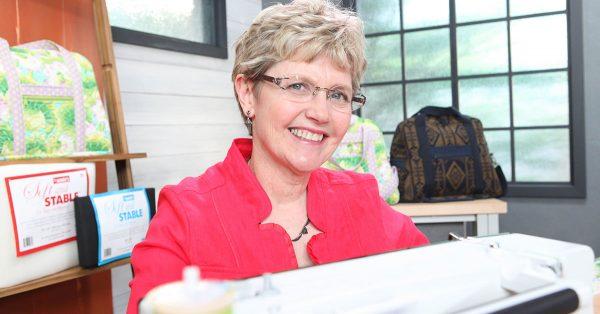 Woman smiling near a sewing machine