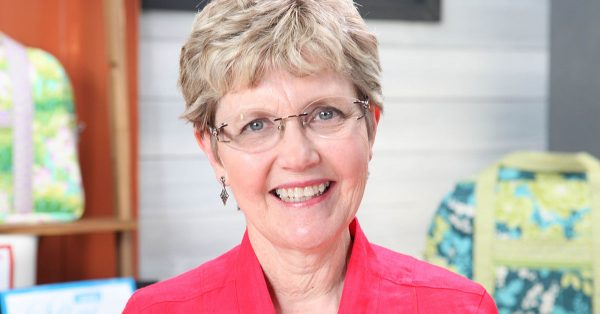 Woman with short hair and glasses smiling at the camera