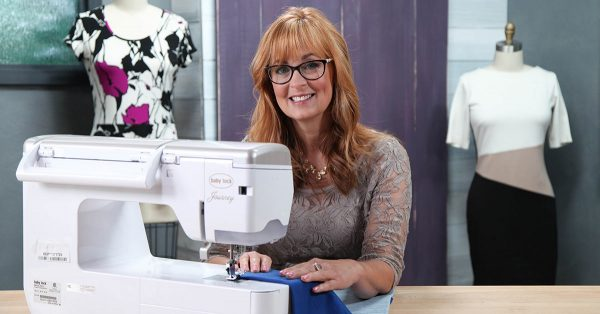 Woman smiling in front of a sewing machine