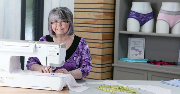 Woman in a purple shirt using a sewing machine