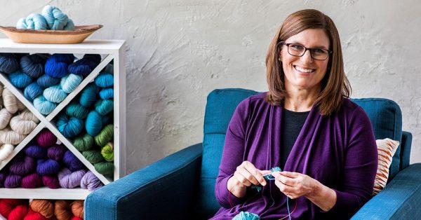 Woman knitting in a dark blue chair