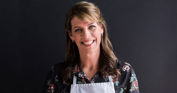 Woman in an apron smiling at the camera
