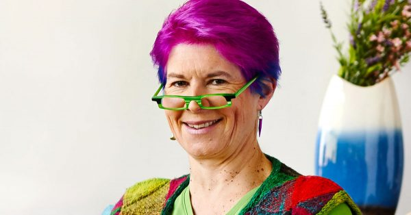 Woman with short purple hair and bright green glasses smiling at camera