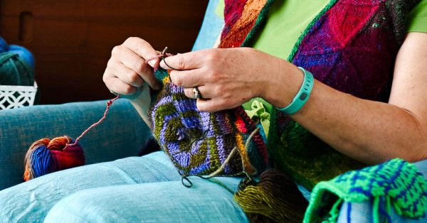 Person knitting with colorful yarn