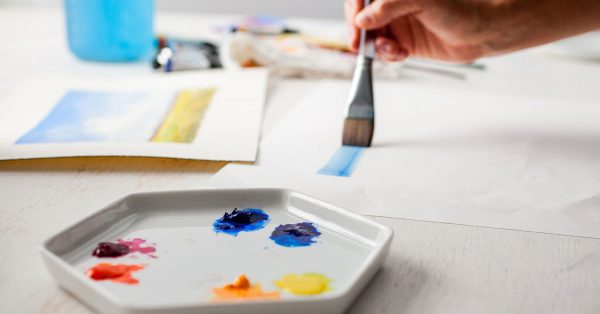 Person painting with blue paint