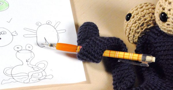 Knit animal holding a pencil