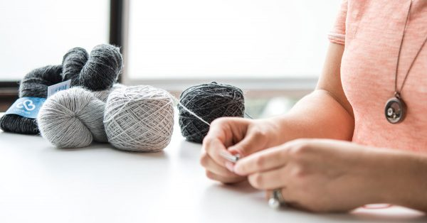 Woman knitting with colors of grey yarn