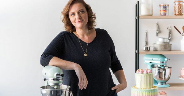 Woman in a black shirt posing on a kitchen aid mixer