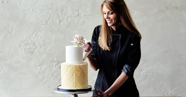 Piping diagonal frosting lines on cake