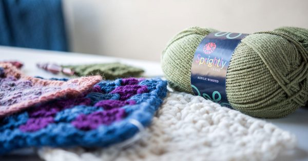 Knit squares and a green roll of yarn