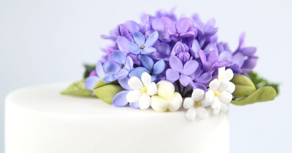 Purple and white sugar flowers on a cake