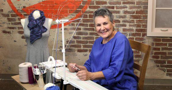 Woman smiling near a knitting machine