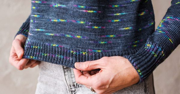 Person holding the hem of a knit sweater