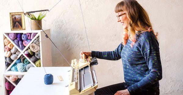 Woman in glasses machine knitting