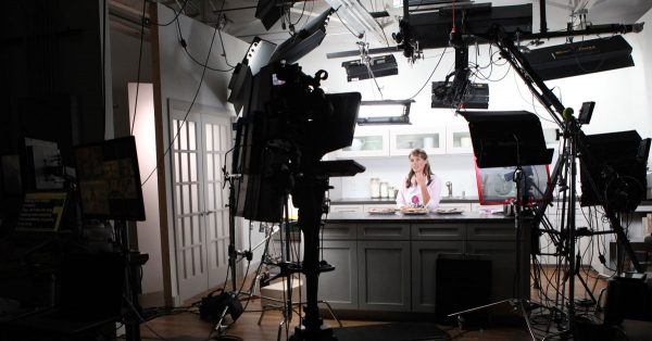 Behind the scenes of cameras at a woman in a kitchen