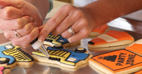 Decorating sugar cookies with construction theme