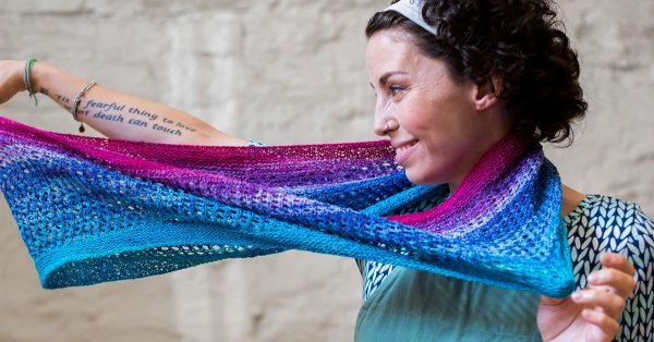Woman holding a colorful blue pink and purple knit scarf