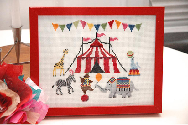 Cross-stitch pattern of circus tent surrounded by animals