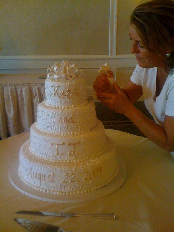 Woman Decorating a Tiered Wedding Cake