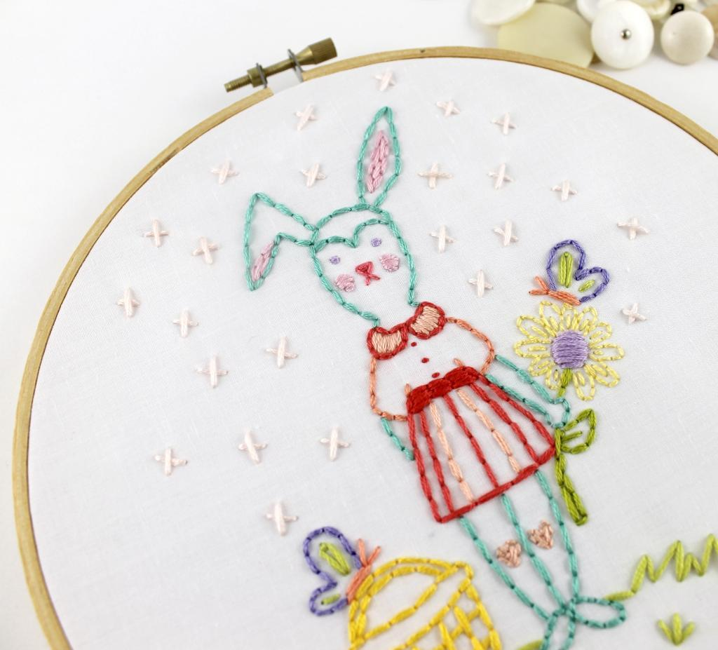 hand embroidery pattern of a rabbit in a dress holding a flower