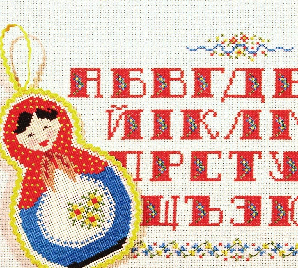 Alphabet sampler of cyrillic letters in red with russian doll