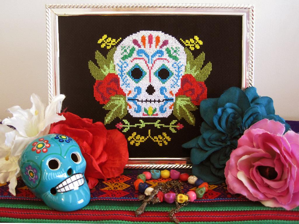 Cross stitch sugar skull surrounded by flowers