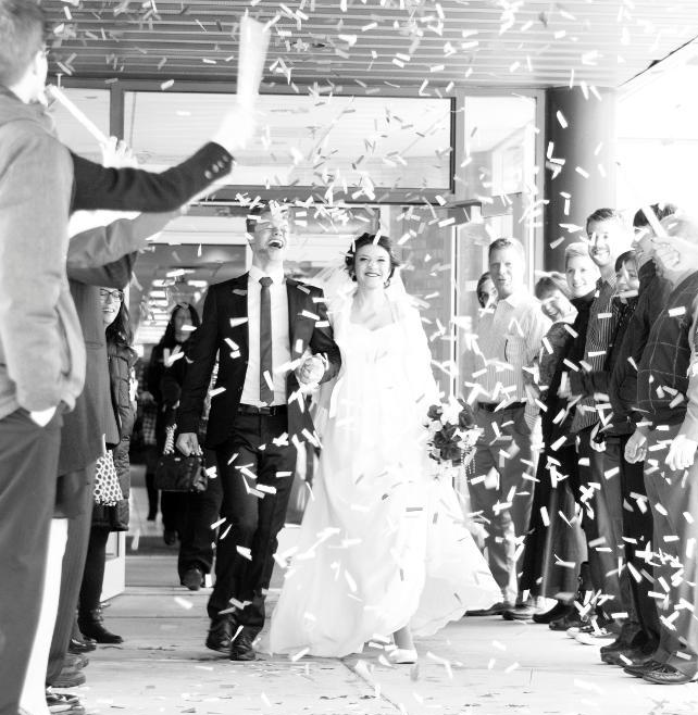 Group Tossing   Flower Petals at Wedding Couple